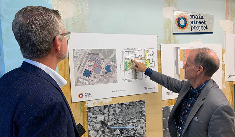 Rick Lees of Main Street Project shows Kevin Van of Qualico the new building plans