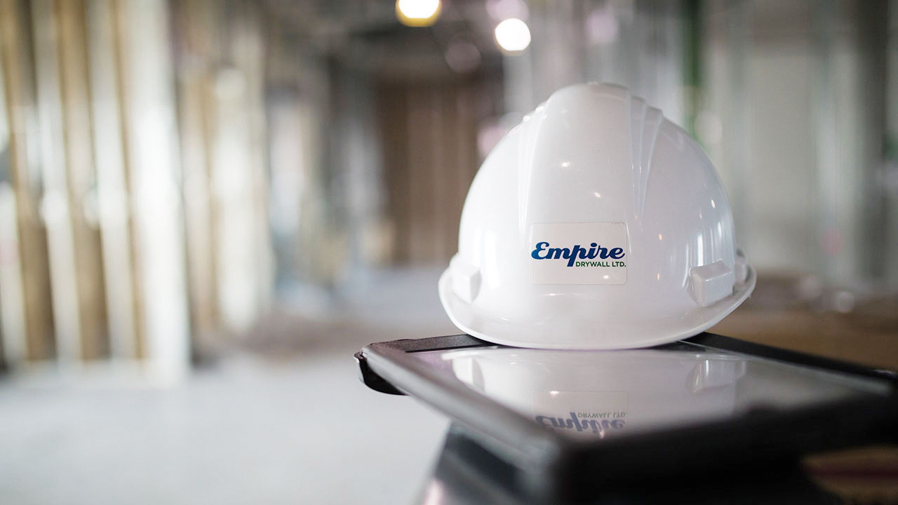 An Empire Drywall hardhat sits on top of a tablet..