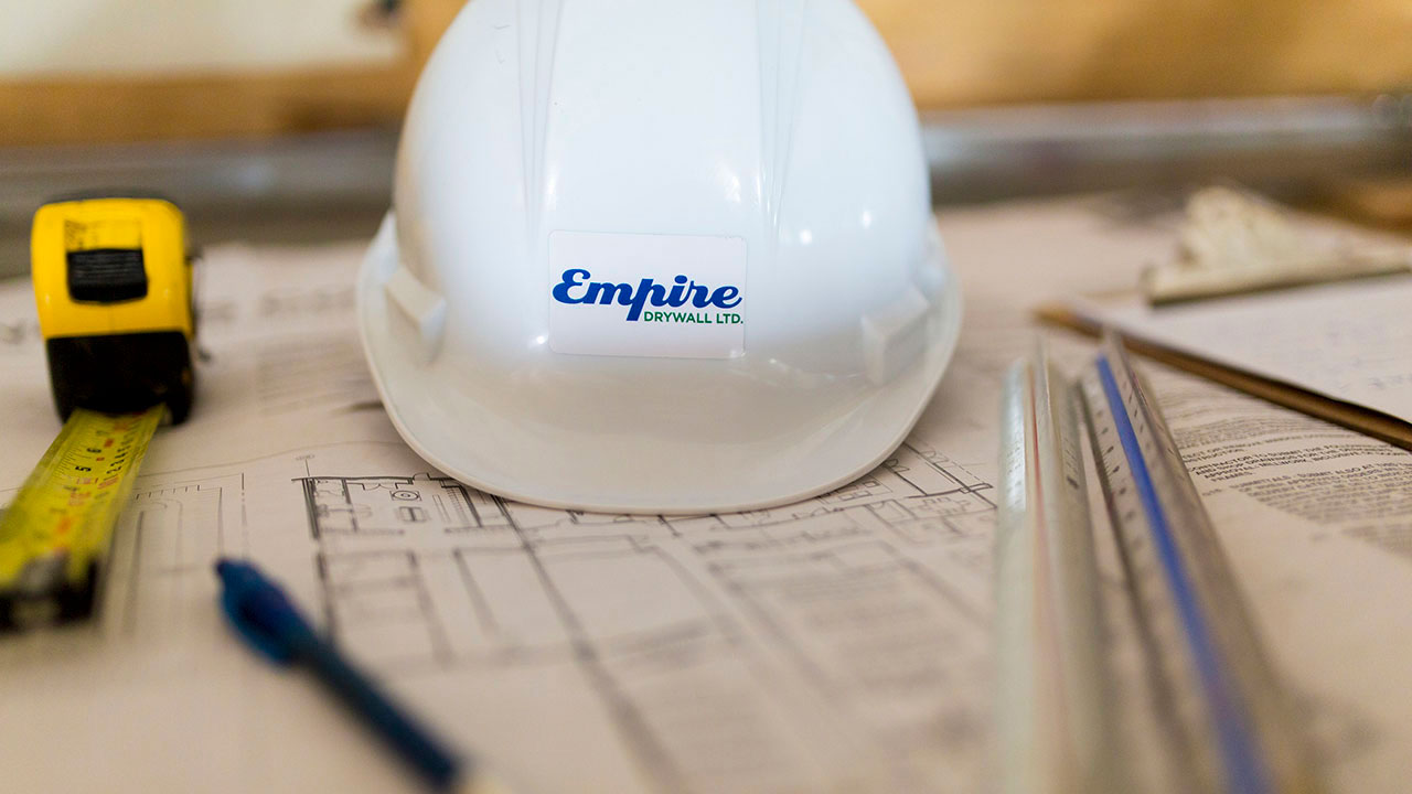 Empire Drywall hard hat sits on construction plans.