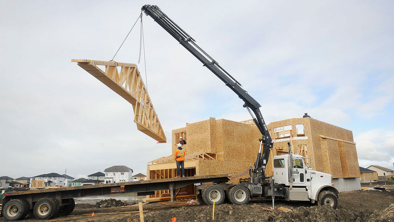 A Star Truss worker is unloading trusses for a home.