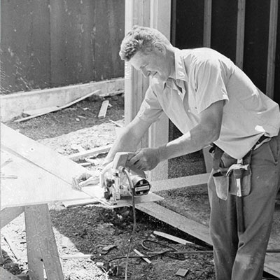 historical image of man cutting wood on job site.